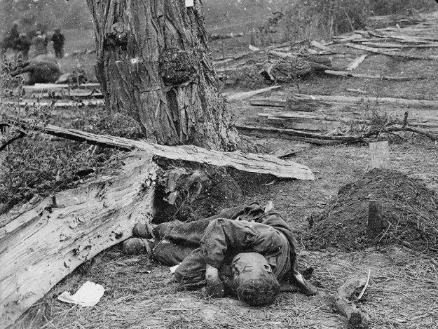 """Gardner's caption for this photograph: """"A Contrast: Federal buried, Confederate unburied, where they fell on the Battle-field of Antietam."""""""